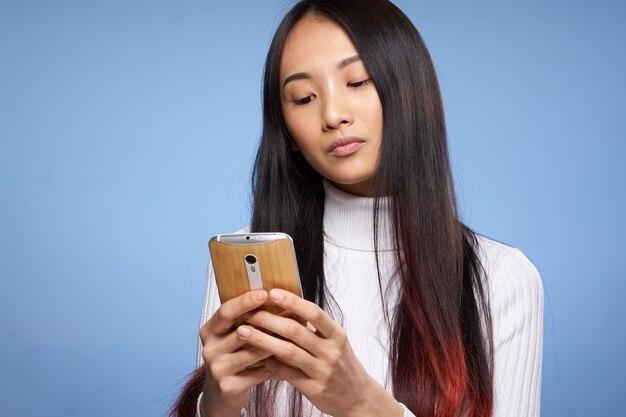 Junge asiatische frau, die mit ihrem telefon aufwirft