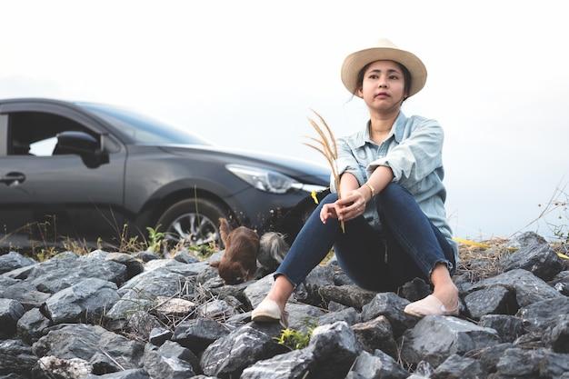 Junge asiatische frau, die mit ihren hunden neben der straße mit schwarzem auto- und meilenstein sitzt.