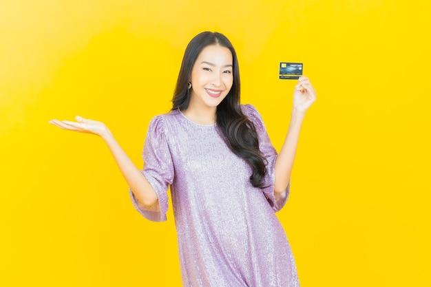 Junge asiatische frau, die mit kreditkarte auf gelb lächelt