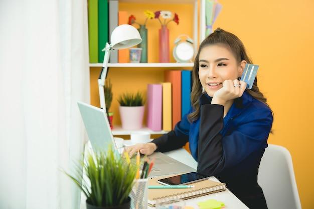 Junge asiatische frau, die mit kreditkarte zahlt