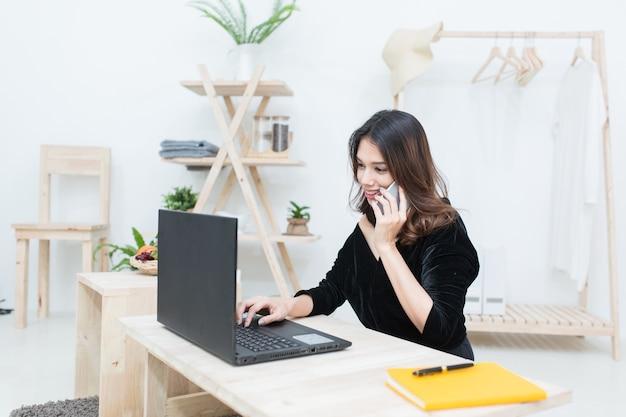 Junge asiatische frau, die mit laptop arbeitet und das geschäft des smartphones zu hause spricht
