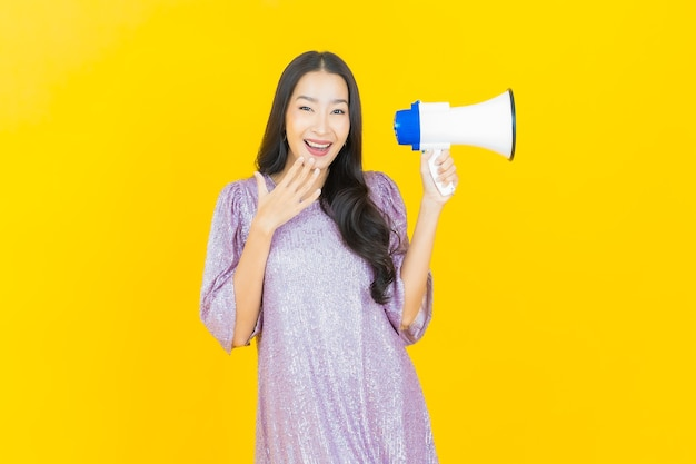 Junge asiatische frau, die mit megaphon auf gelb lächelt