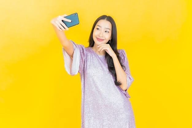 Junge asiatische frau, die mit smartphone auf gelb lächelt