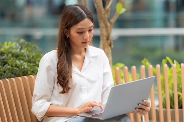 Junge asiatische frau, die mit smileygesicht unter verwendung des laptops in einer stadt sitzt