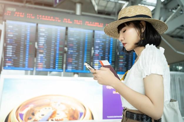 Junge asiatische frau, die mobile im flughafen für die prüfung ihres flugeinstiegs verwendet,