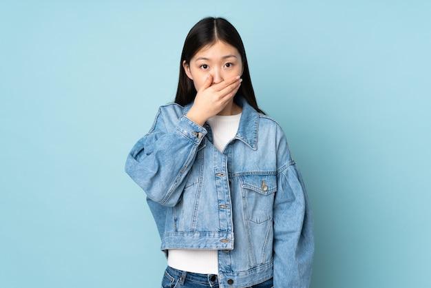 Junge asiatische frau, die mund mit hand bedeckt