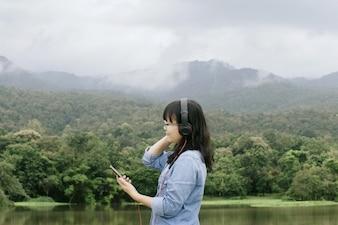 Junge asiatische Frau, die Musik an ihrem Handy im Park genießt und hört.