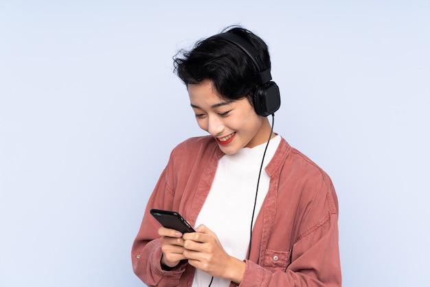 Junge asiatische frau, die musik hört und auf handy schaut