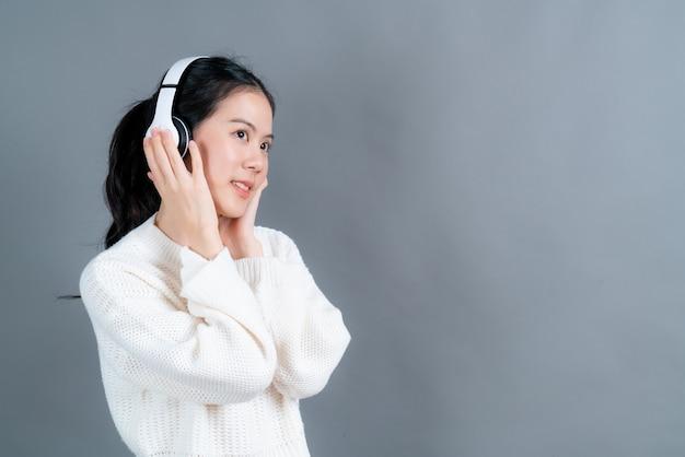 Junge asiatische frau, die musik mit kopfhörern auf grauer wand hört und genießt
