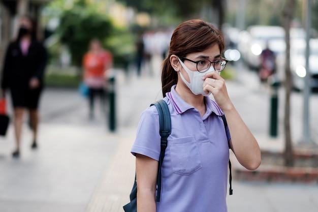 Junge asiatische frau, die n95 atemmaske trägt, schützt und filtert pm2.5 (feinstaub) gegen verkehr und staubstadt. gesundheits- und luftverschmutzungskonzept
