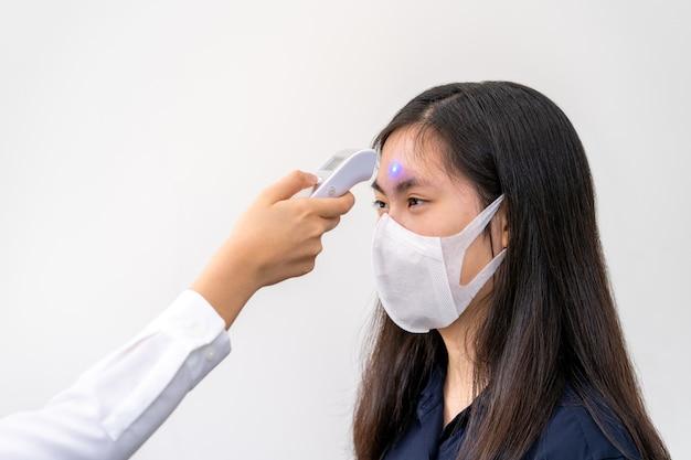 Junge asiatische frau, die n95-maske trägt und ihren temperaturcheck erhält
