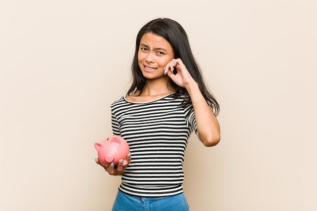 Junge asiatische frau, die ohren einer sparschweinbedeckung mit den händen hält.