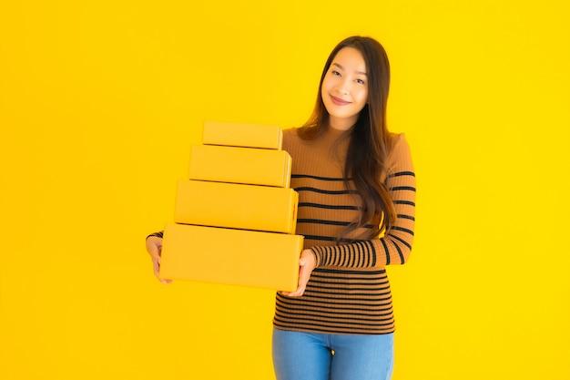 Junge asiatische frau, die pappkarton in ihrer hand auf gelb hält