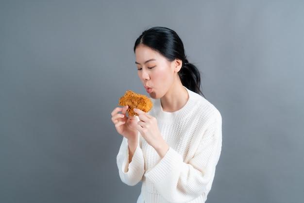 Junge asiatische frau, die pullover mit glücklichem gesicht trägt und genießt, gebratenes huhn auf grauem hintergrund zu essen