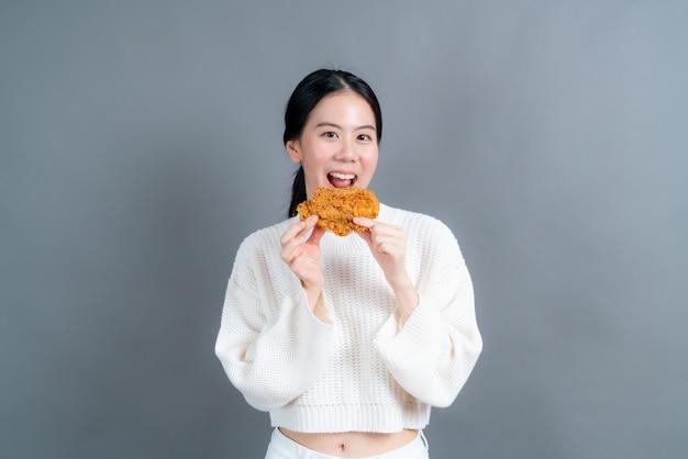 Junge asiatische frau, die pullover mit glücklichem gesicht trägt und genießt, gebratenes huhn auf grauer wand zu essen