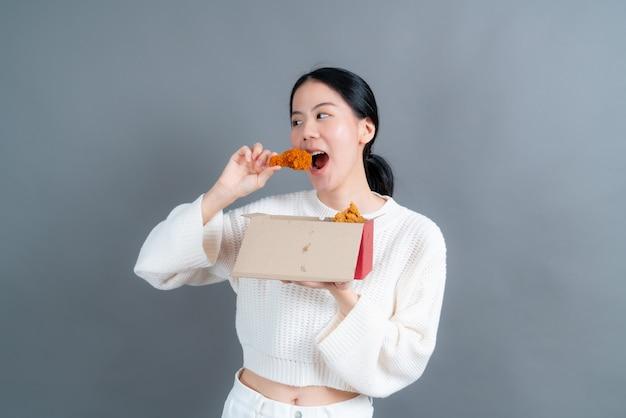 Junge asiatische frau, die pullover mit glücklichem gesicht trägt und genießt, gebratenes huhn zu essen
