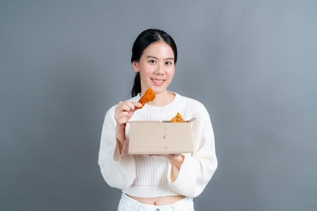 Junge asiatische frau, die pullover mit glücklichem gesicht trägt und gerne gebratenes huhn isst