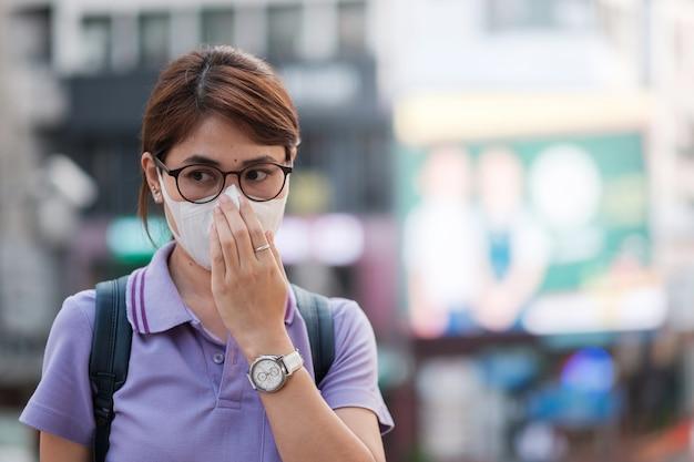 Junge asiatische frau, die schutzmaske gegen grippevirus in der stadt trägt. gesundheits- und luftverschmutzungskonzept