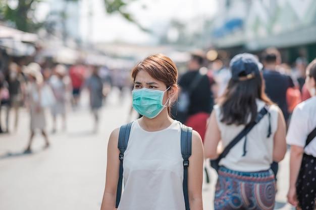 Junge asiatische frau, die schutzmaske gegen neuartiges coronavirus (2019-ncov) oder wuhan coronavirus am chatuchak-wochenendmarkt trägt, wahrzeichen und beliebt für touristenattraktionen