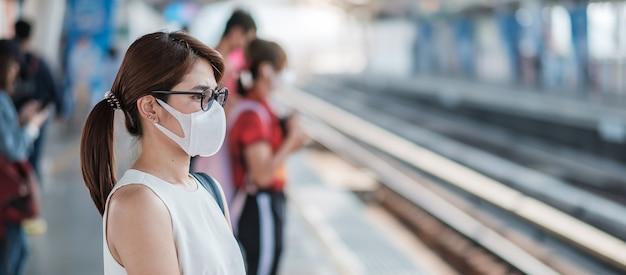 Junge asiatische frau, die schutzmaske gegen neuartiges coronavirus (2019-ncov) oder wuhan coronavirus am öffentlichen bahnhof trägt, ist ein ansteckendes virus, das atemwegsinfektion verursacht