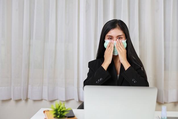 Junge asiatische frau, die schutzmaske im büro sitzt und an computer-laptop und smartphone arbeitet.