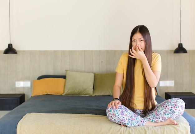 Junge asiatische frau, die sich angewidert fühlt und die nase hält, um einen üblen und unangenehmen gestank zu vermeiden
