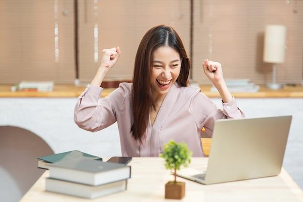 Junge asiatische frau, die sich beim betrachten des laptops für den start des kleinen unternehmens zu hause aufgeregt fühlt