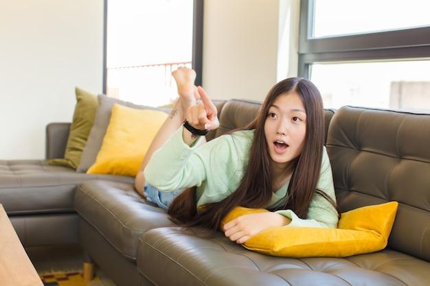 Junge asiatische frau, die sich schockiert und überrascht fühlt, ehrfürchtig zeigt und mit erstauntem blick mit offenem mund nach oben schaut