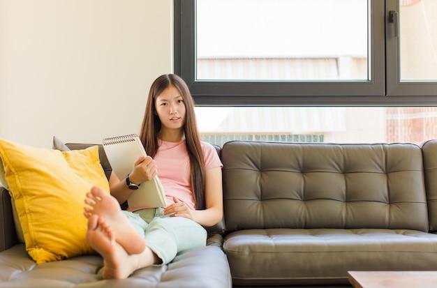 Junge asiatische frau, die sich verwirrt und verwirrt fühlt, mit einem dummen, fassungslosen ausdruck, der etwas unerwartetes betrachtet