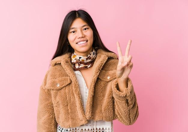 Junge asiatische frau, die siegeszeichen zeigt und breit lächelt.