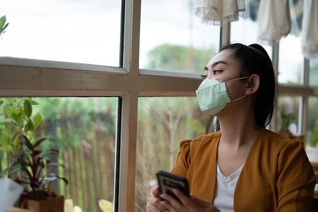Junge asiatische frau, die sitzt und eine medizinische maske aufsetzt, um durch virusinfektion luftgetragene atemwegserkrankungen zu schützen, schaute sie zum fenster im café