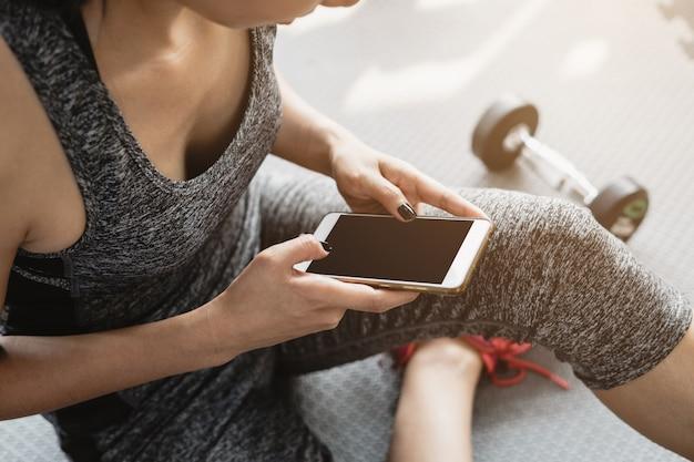 Junge asiatische frau, die smartphone in der turnhalle verwendet