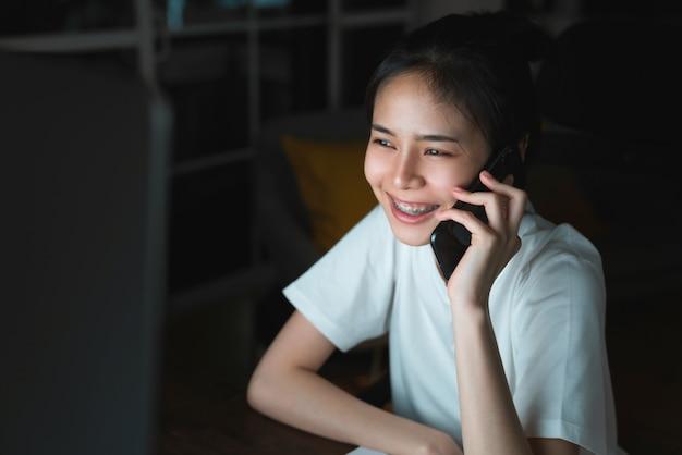 Junge asiatische frau, die smartphone und computer auf tisch in der nacht zu hause anruft.