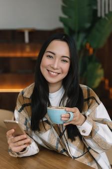 Junge asiatische frau, die smartphone verwendet, kaffee im café trinkend