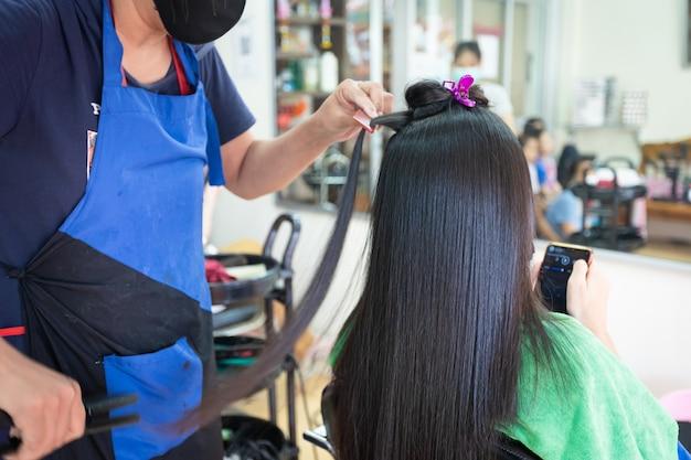 Junge asiatische frau, die smartphone verwendet, während sie ein glattes haar mit haarglätter vom friseur bekommt. schönheitssalon, haarpflegekonzept.