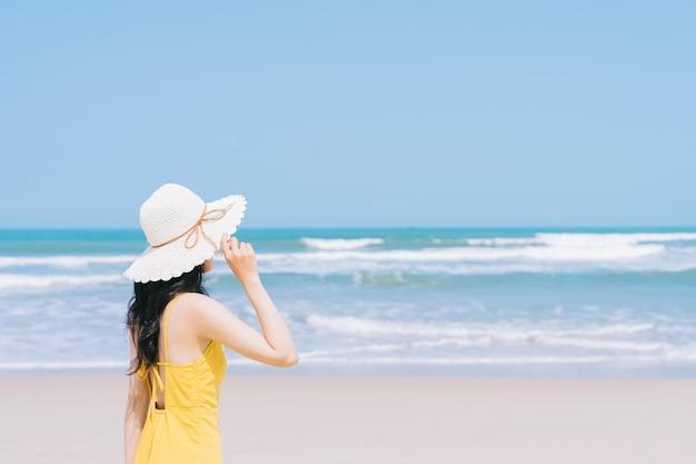 Junge asiatische frau, die sommerferien am strand genießt
