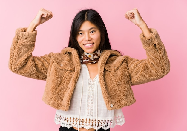 Junge asiatische frau, die stärkegeste mit den armen, symbol der weiblichen energie zeigt