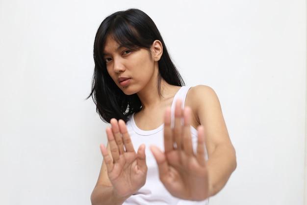 Junge asiatische frau, die stoppgeste mit ihrer hand lokalisiert macht