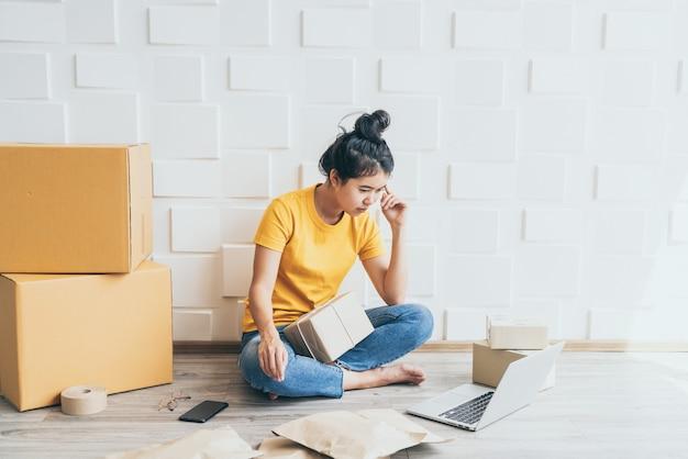 Junge asiatische frau, die stress oder depression vor ihrem laptop fühlt