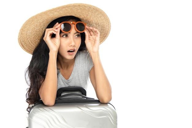 Junge asiatische frau, die strohhut und sonnenbrille mit breiter krempe trägt
