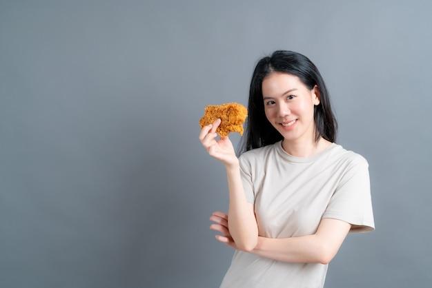 Junge asiatische frau, die t-shirt mit glücklichem gesicht trägt und genießt, gebratenes huhn zu essen