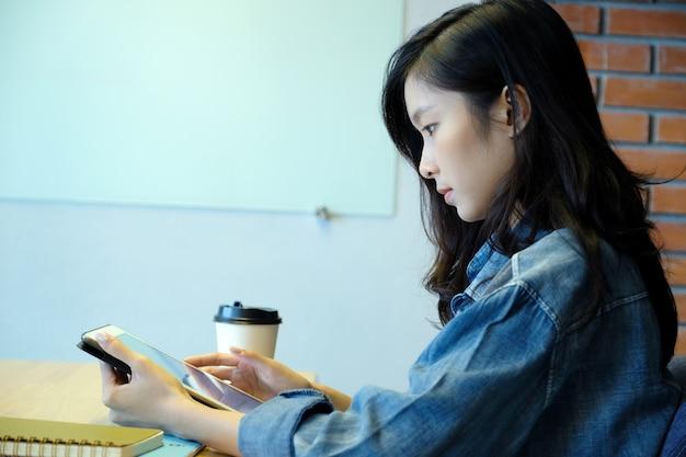 Junge asiatische frau, die tablette beim sitzen im raumhintergrund, in den leuten und in der technologie, l verwendet