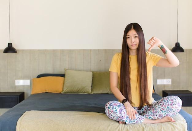 Junge asiatische frau, die traurig, enttäuscht oder wütend aussieht, daumen in uneinigkeit zeigt und sich frustriert fühlt
