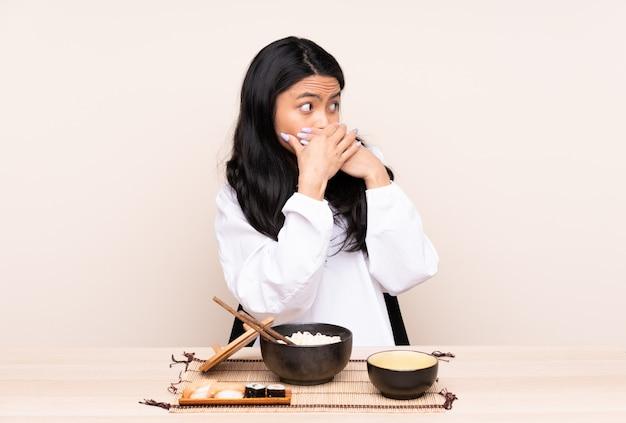 Junge asiatische frau, die über isolierte wand isst