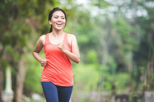 Junge asiatische frau, die übung im freien in einem park macht, joggend