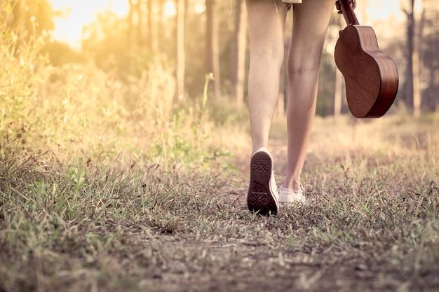 Junge asiatische frau, die ukulele hält und in den park im weinlesefarbton geht