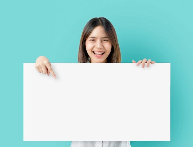 Junge asiatische frau, die unbelegtes papier mit lächelndem gesicht anhält und auf dem blau schaut.