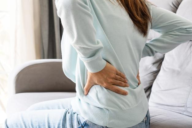 Junge asiatische frau, die unter rückenschmerzen leidet, sitzt zu hause auf der couch im wohnzimmer. konzept für gesundheitliche probleme. nahansicht