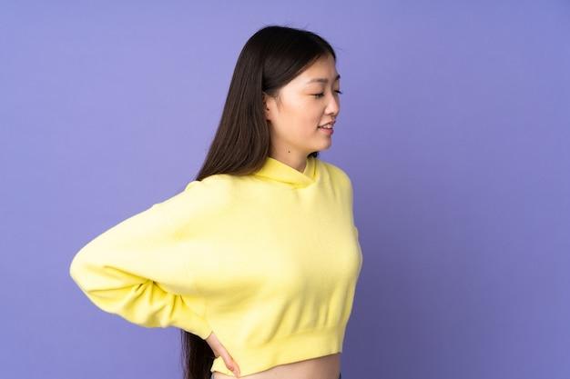Junge asiatische frau, die unter rückenschmerzen leidet