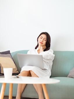 Junge asiatische frau, die unter schmerzen in der schulter leidet, wenn sie einen laptop benutzt